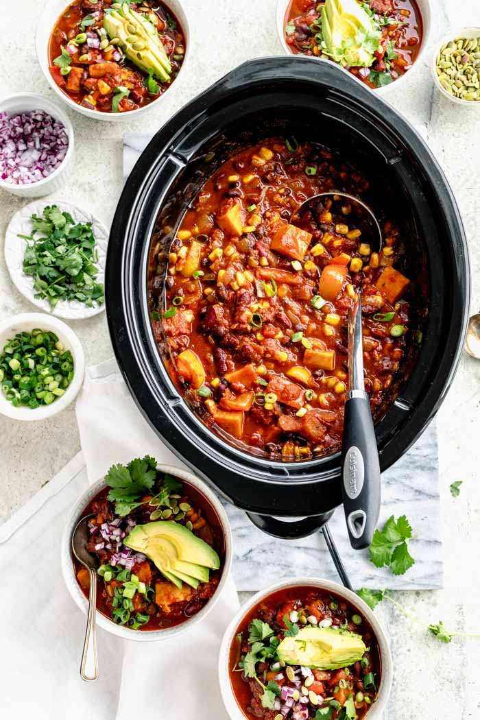Slow Cooker chili in the slow cooker with bowls of chili on the table