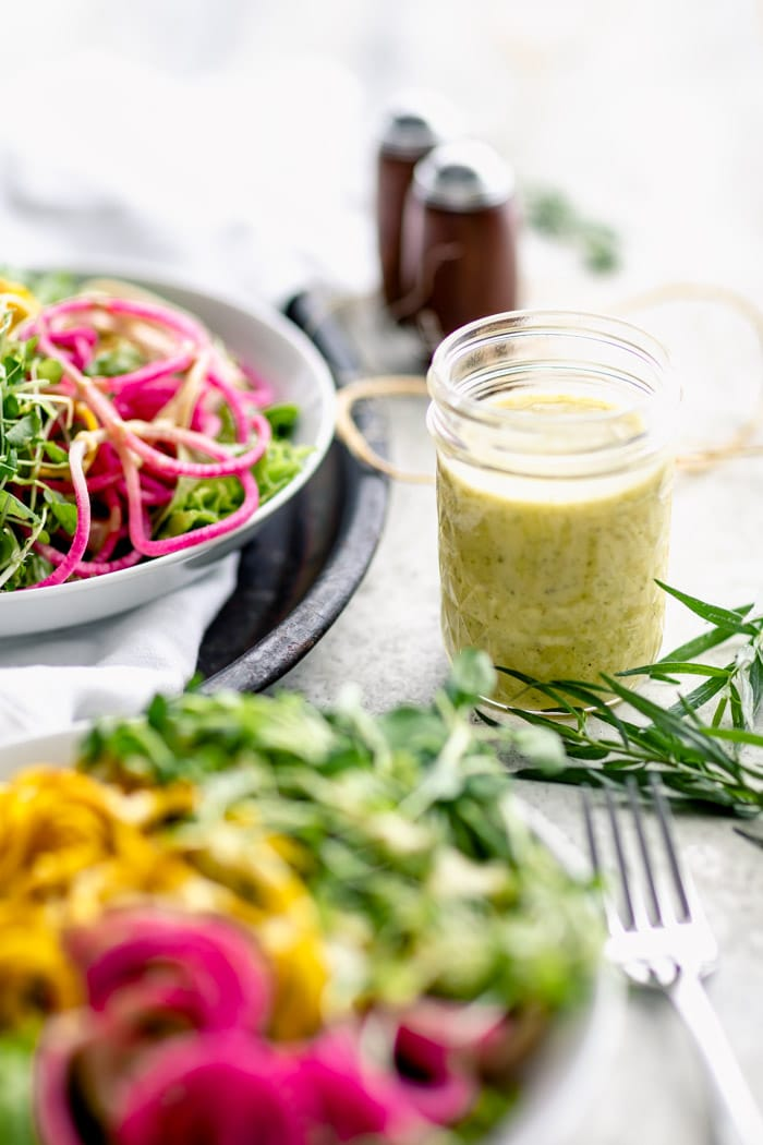 a jar of tarragon vinaigrette dressing on a table with salads