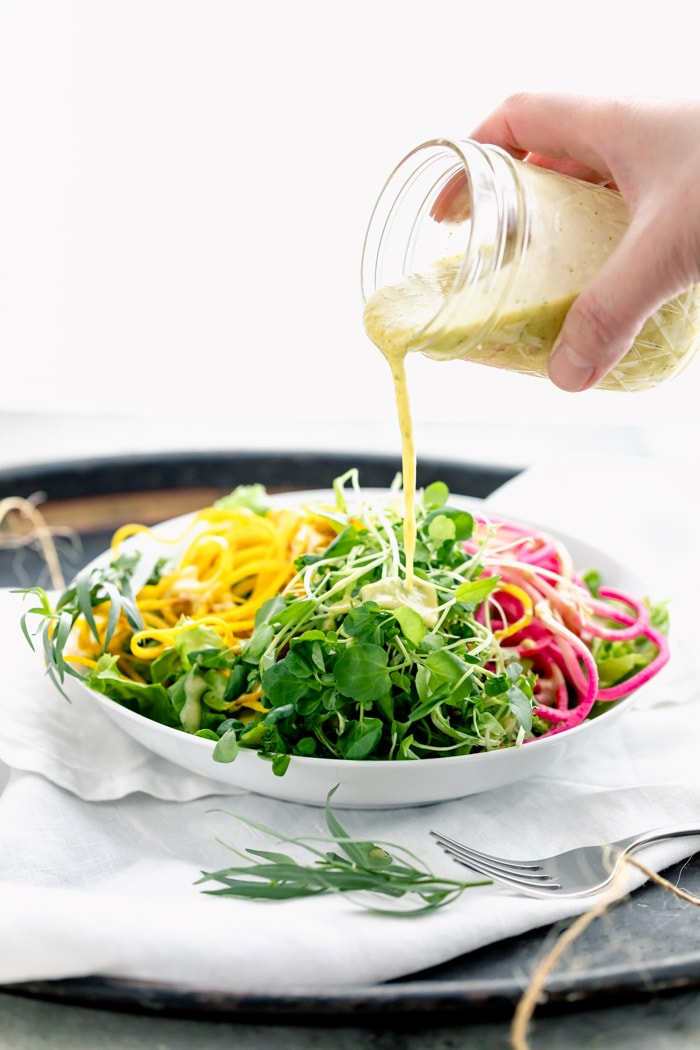 pouring dressing over microgreens and spiralized veggies