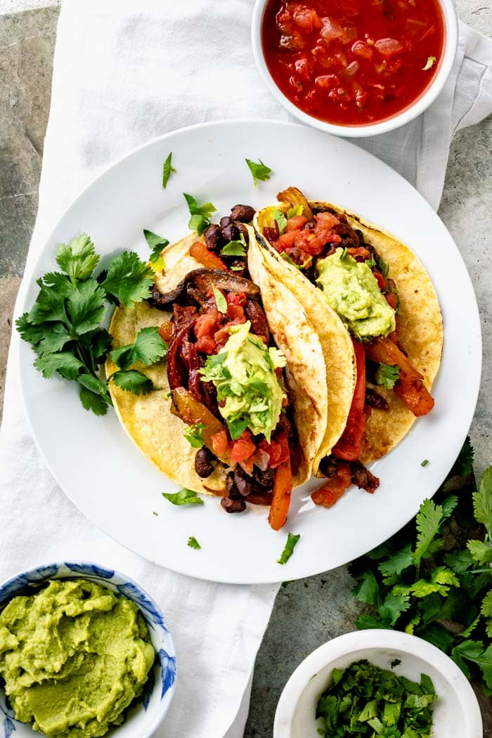 Vegan taco plate from overhead with dishes of toppings set on the side