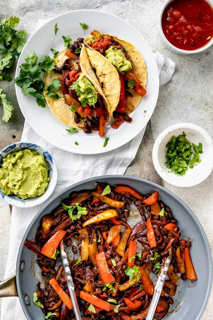 tacos on a plate and a skillet of taco filling from overhead