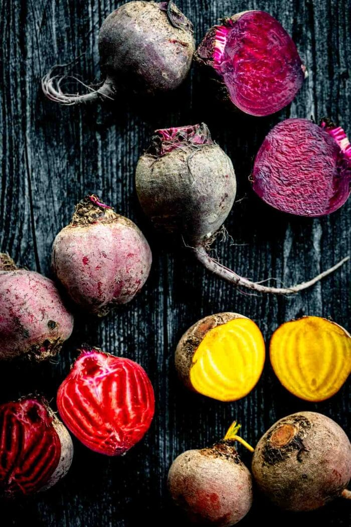 purple, golden and red and white striped beets cut open on a dark wooden table