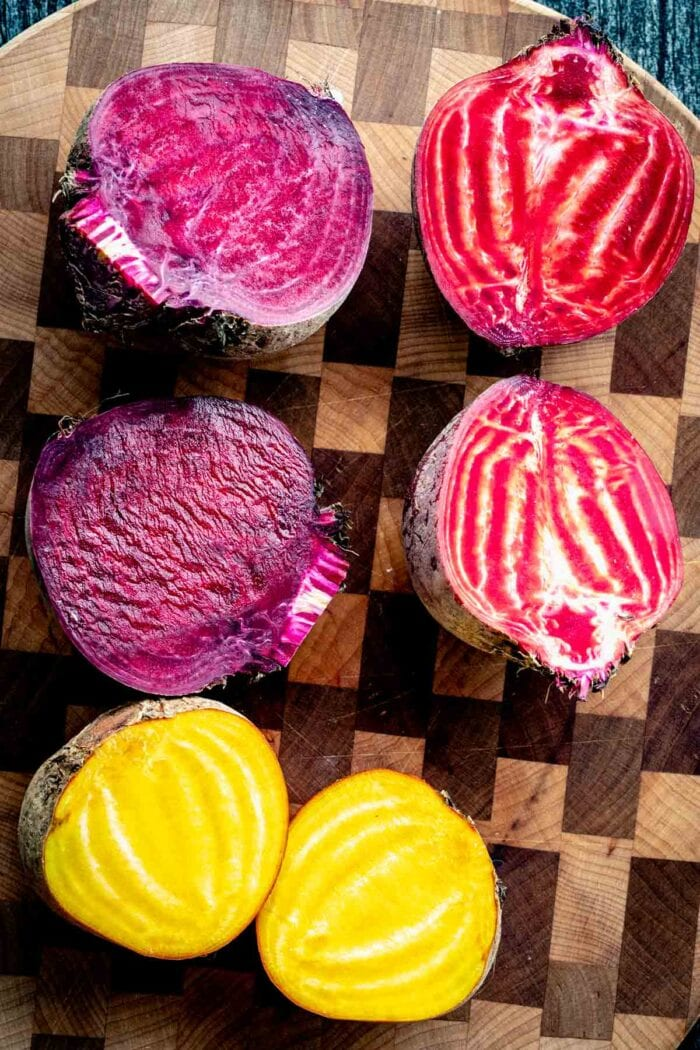 purple, gold, and red and white striped beets on a checkered cutting board
