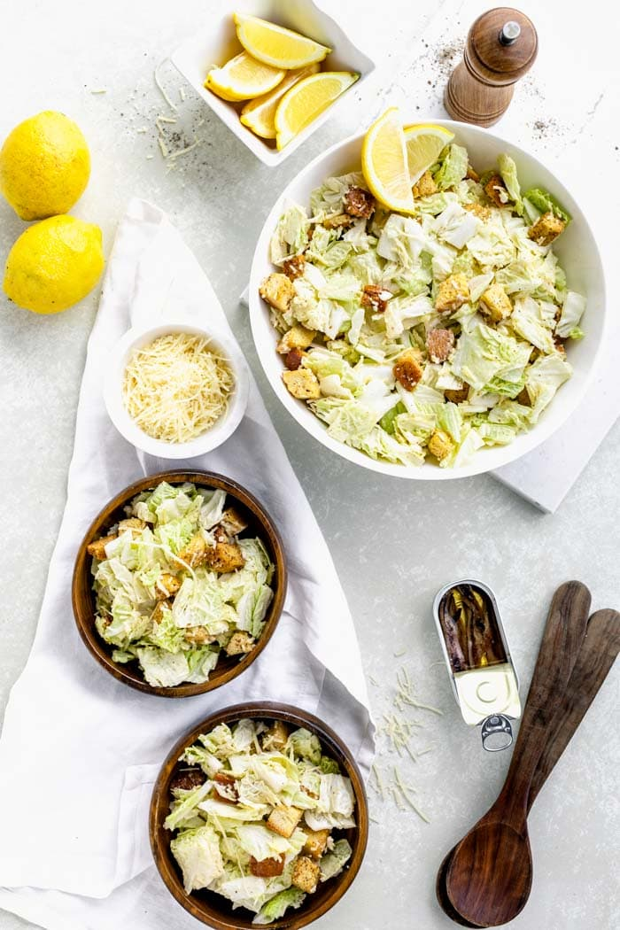 overhead tablescape with bowls of Caesar, anchovies in a tin, lemons and tongs