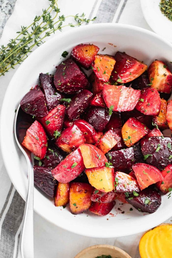 A close-up of a white bowl with colorful roasted beets
