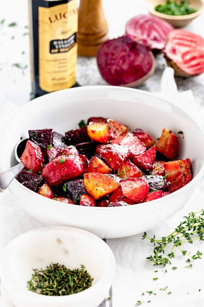 a bowl of beets chunks from the side with a bottle of balsamic vinegar behind it