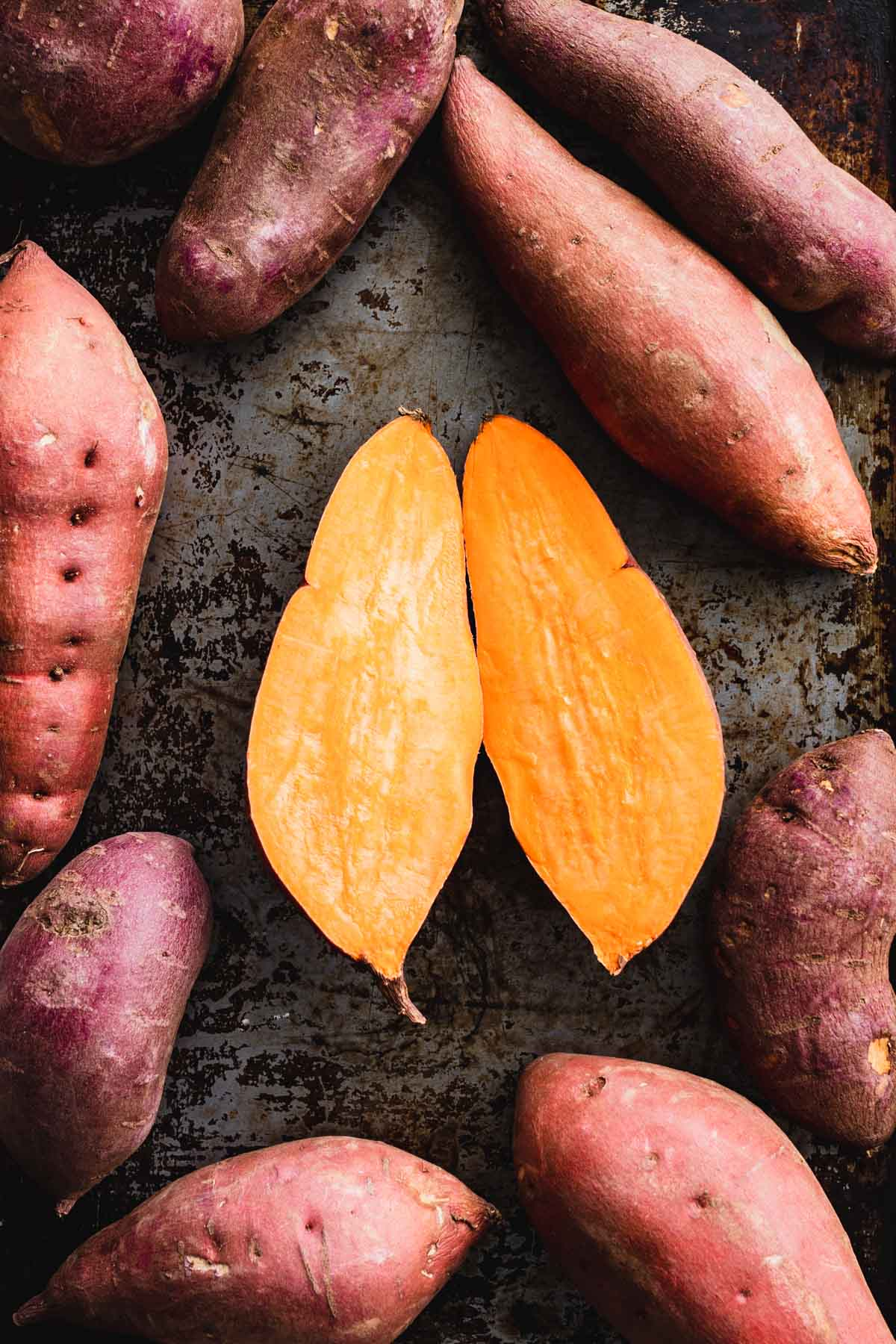 sweet potatoes on a dark background with one split in half