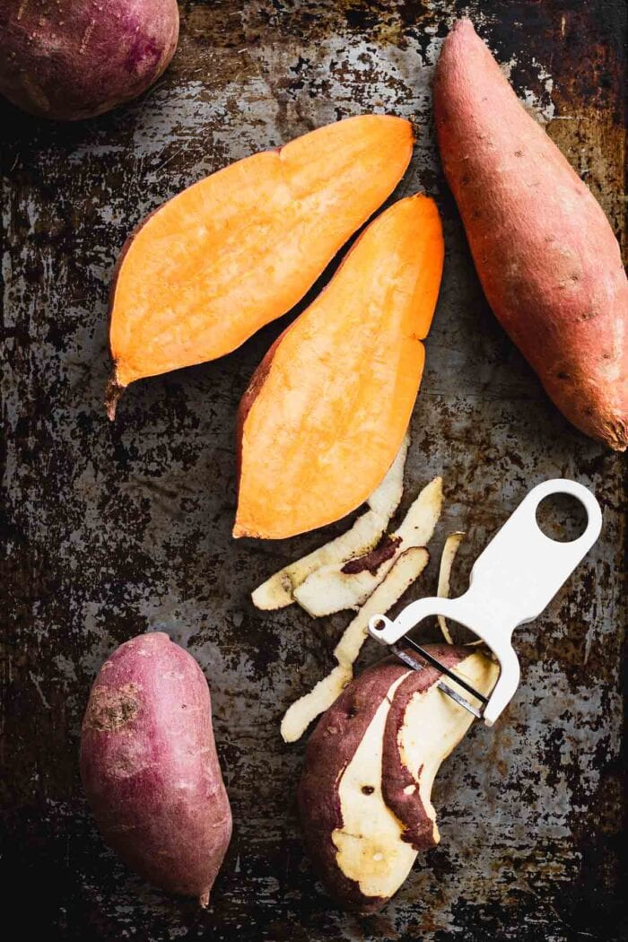 halved orange sweet potato and a peeled white sweet potato.