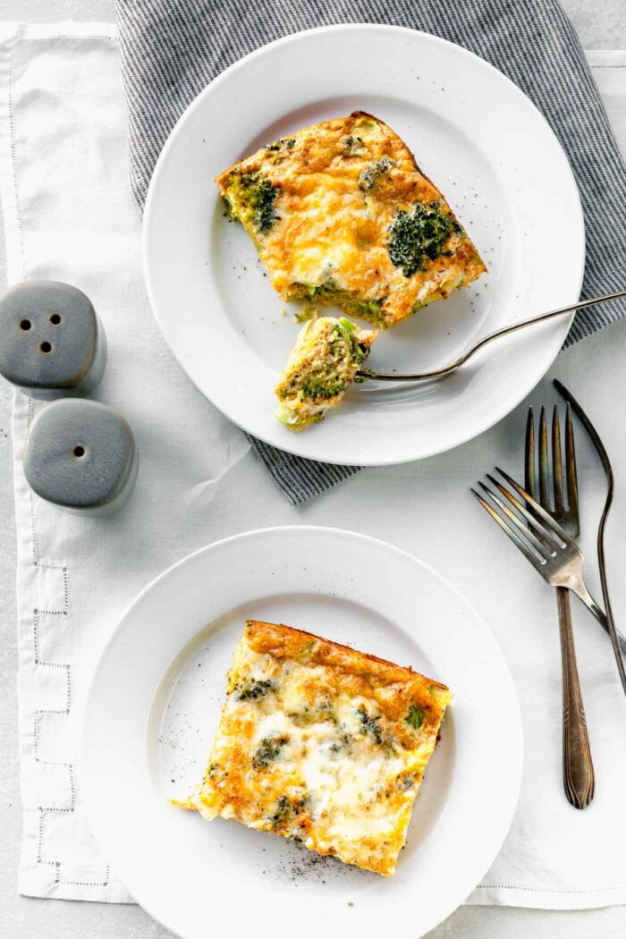 broccoli egg bake slices on white plates with gray salt and pepper shakers