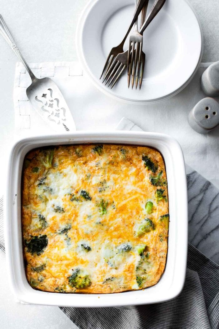 A white square casserole dish with egg bake in it from overhead on a white tablecloth