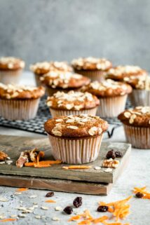 A bunch of muffins sitting on a table with carrots and nuts on the table