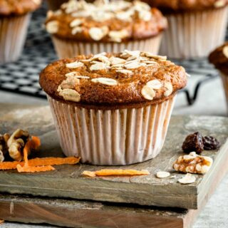 side view of muffin with pieces of carrot and nuts around it