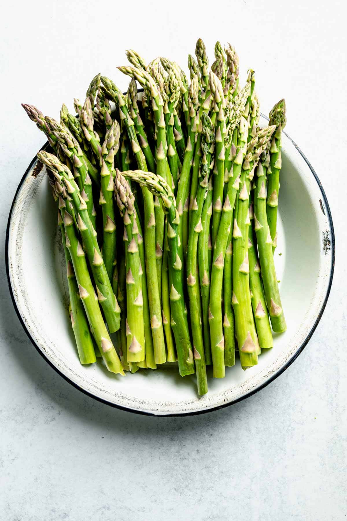 A large bowl of fresh green asparagus stalks.