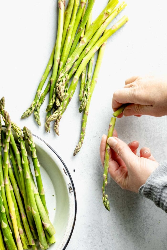 Hands holding a piece of asparagus, a bowl of asparagus sits nearby.