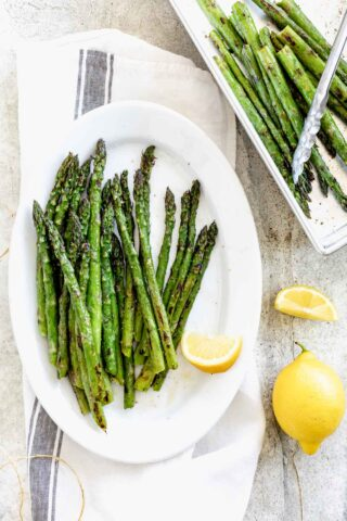 grilled asparagus on a platter with lemons