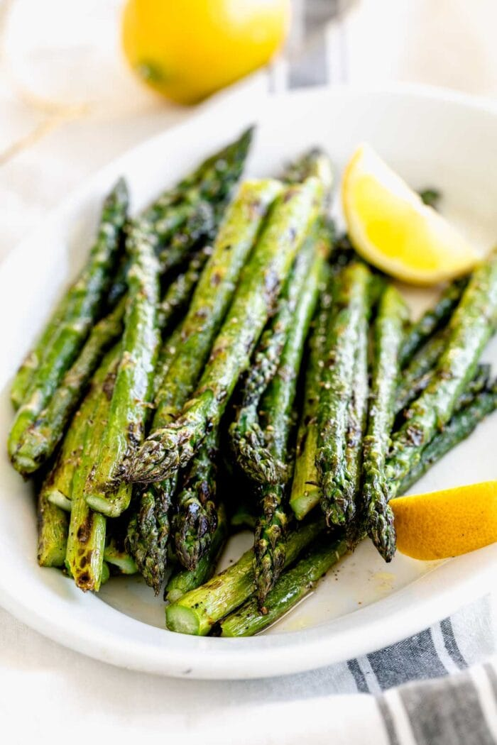 a white oval platter of asparagus with lemon wedges