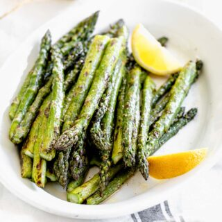a platter of grilled asparagus with lemon wedges