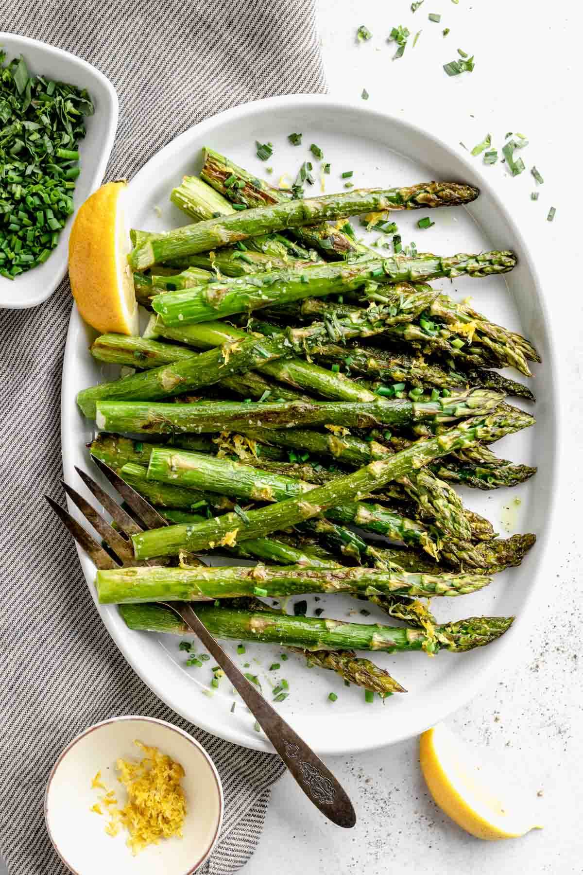 a platter of roasted asparagus with lemon zest, herbs and lemon wedges