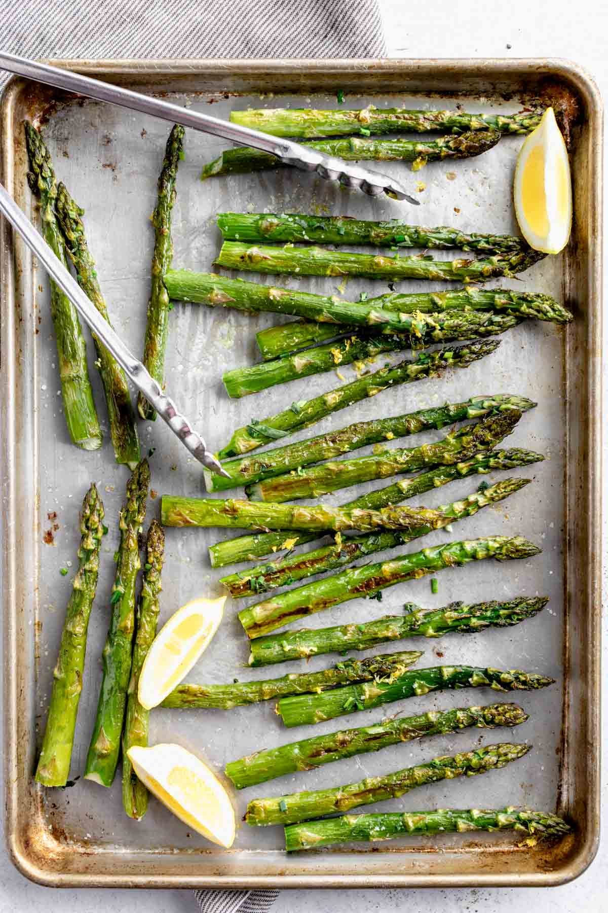 roasted asparagus on a sheet pan with tongs, herbs and lemon wedges