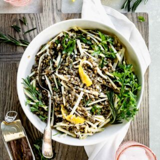 lentil and celery root salad with herbs in a bowl from overhead with pink water glasses