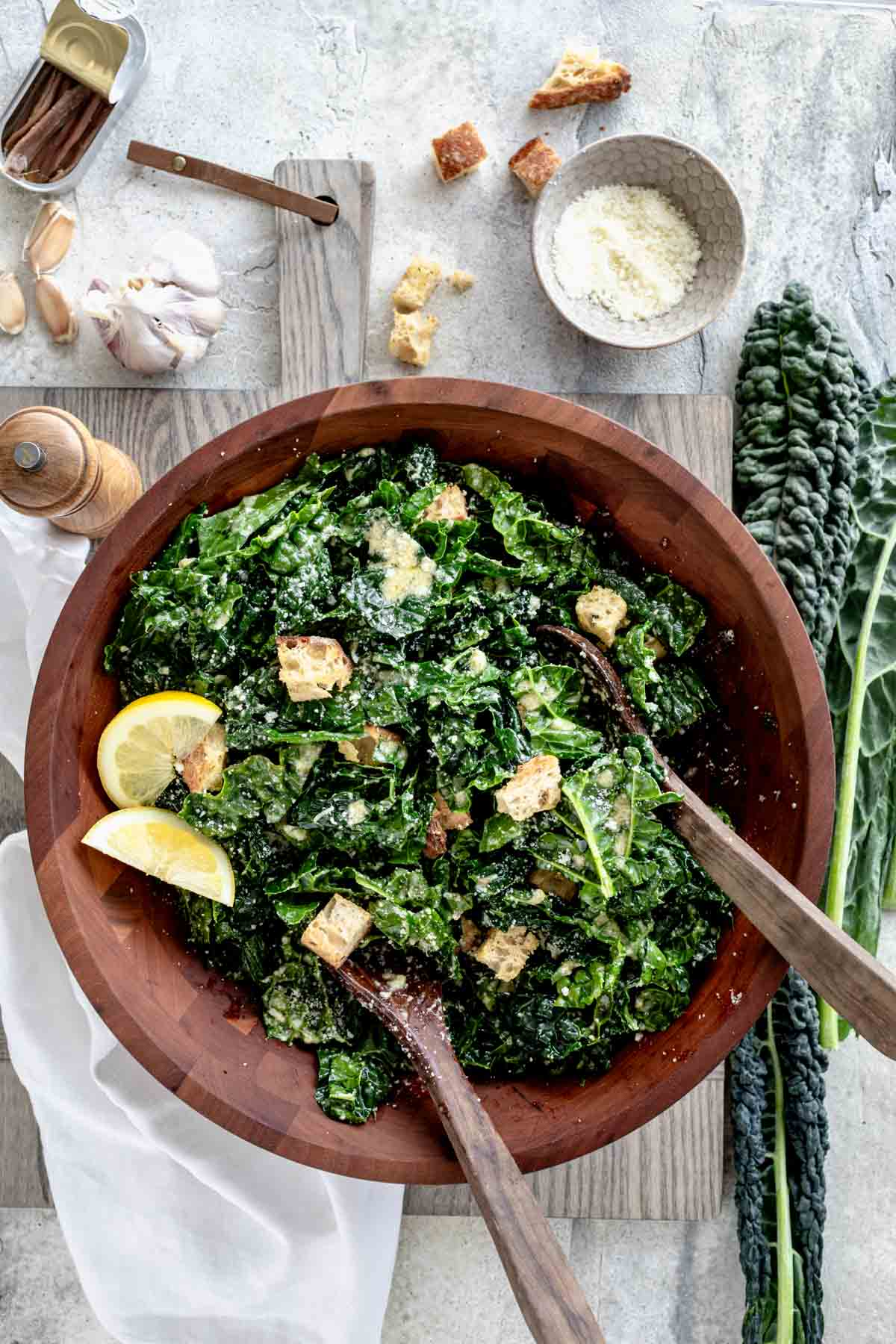 tuscan kale salad in a wooden bowl with salad spoons