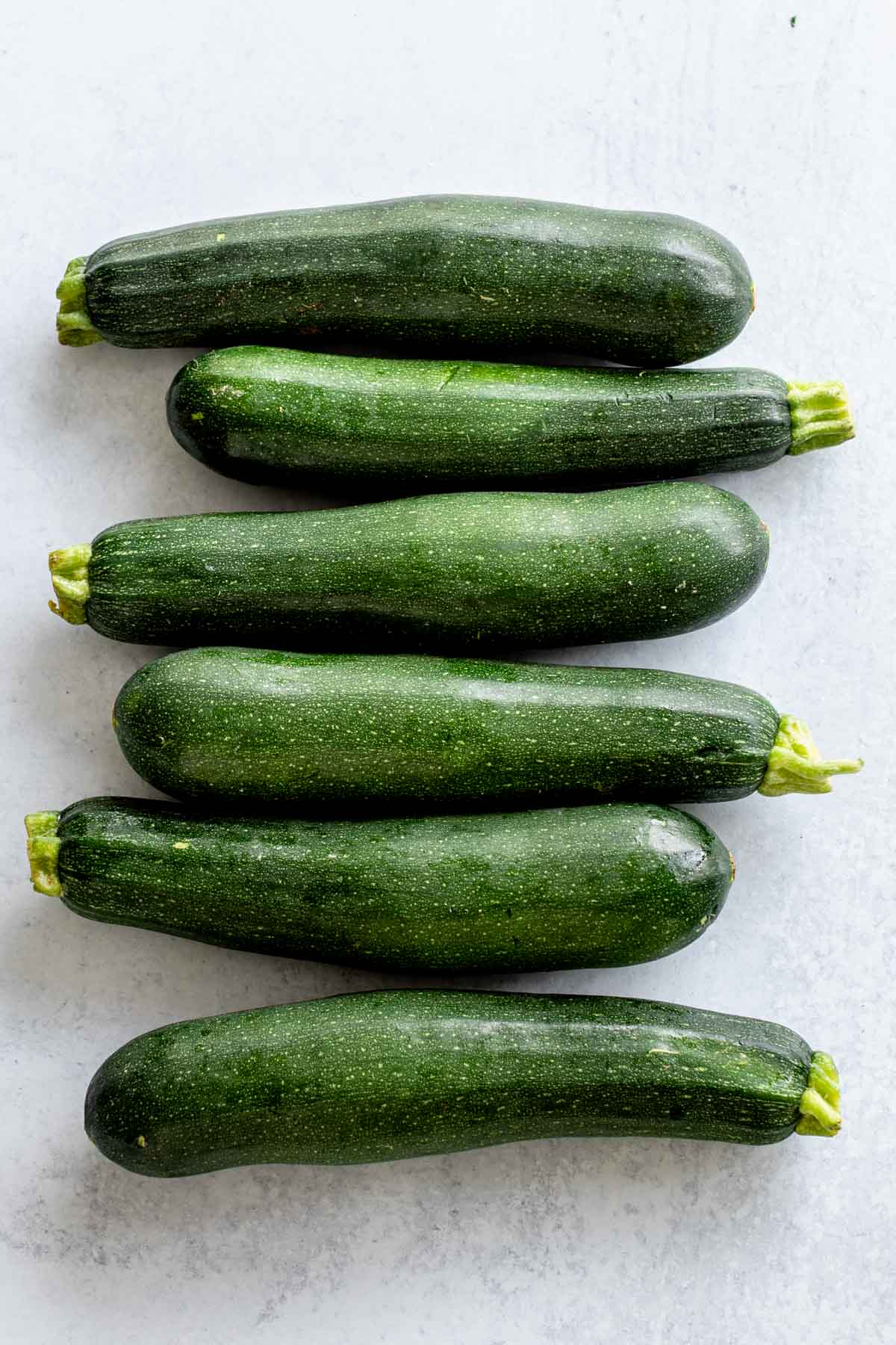six medium, deep green zucchinis on a light colored table