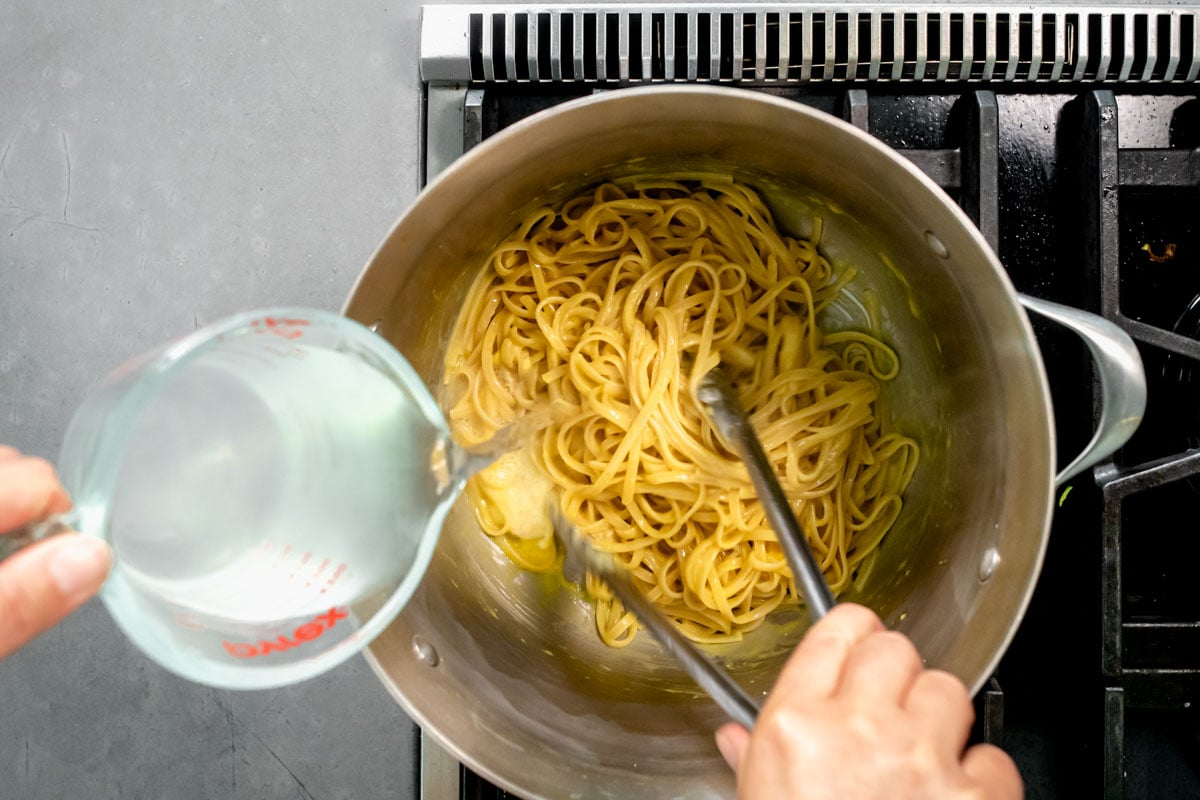 thinning the sauce with the pasta liquid