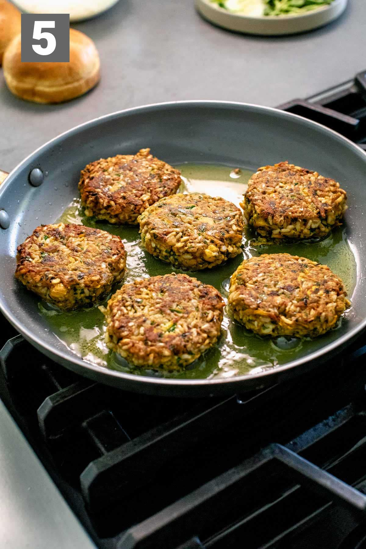 cooking the burgers in the skillet