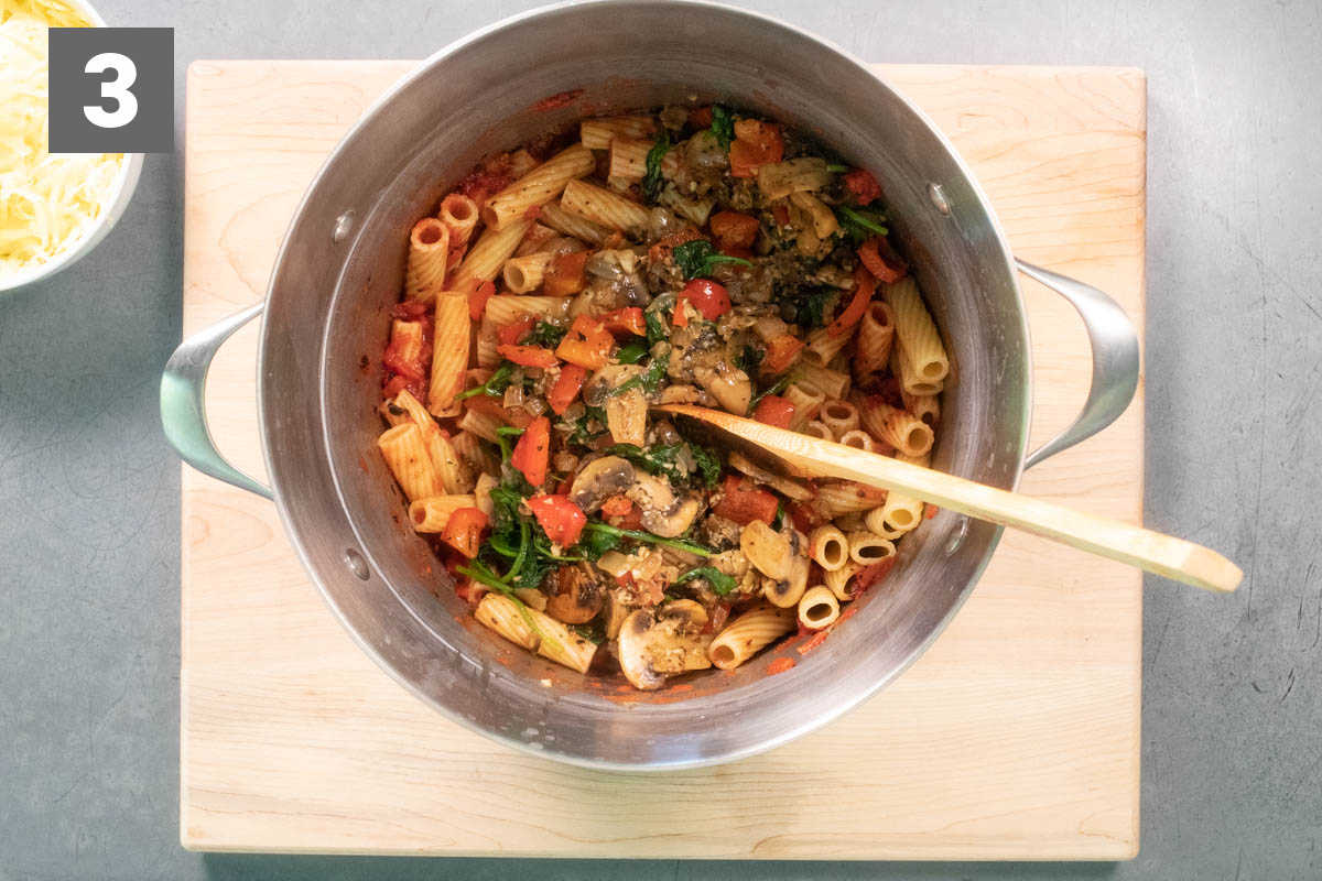 combining the pasta and veggies in the pasta pot