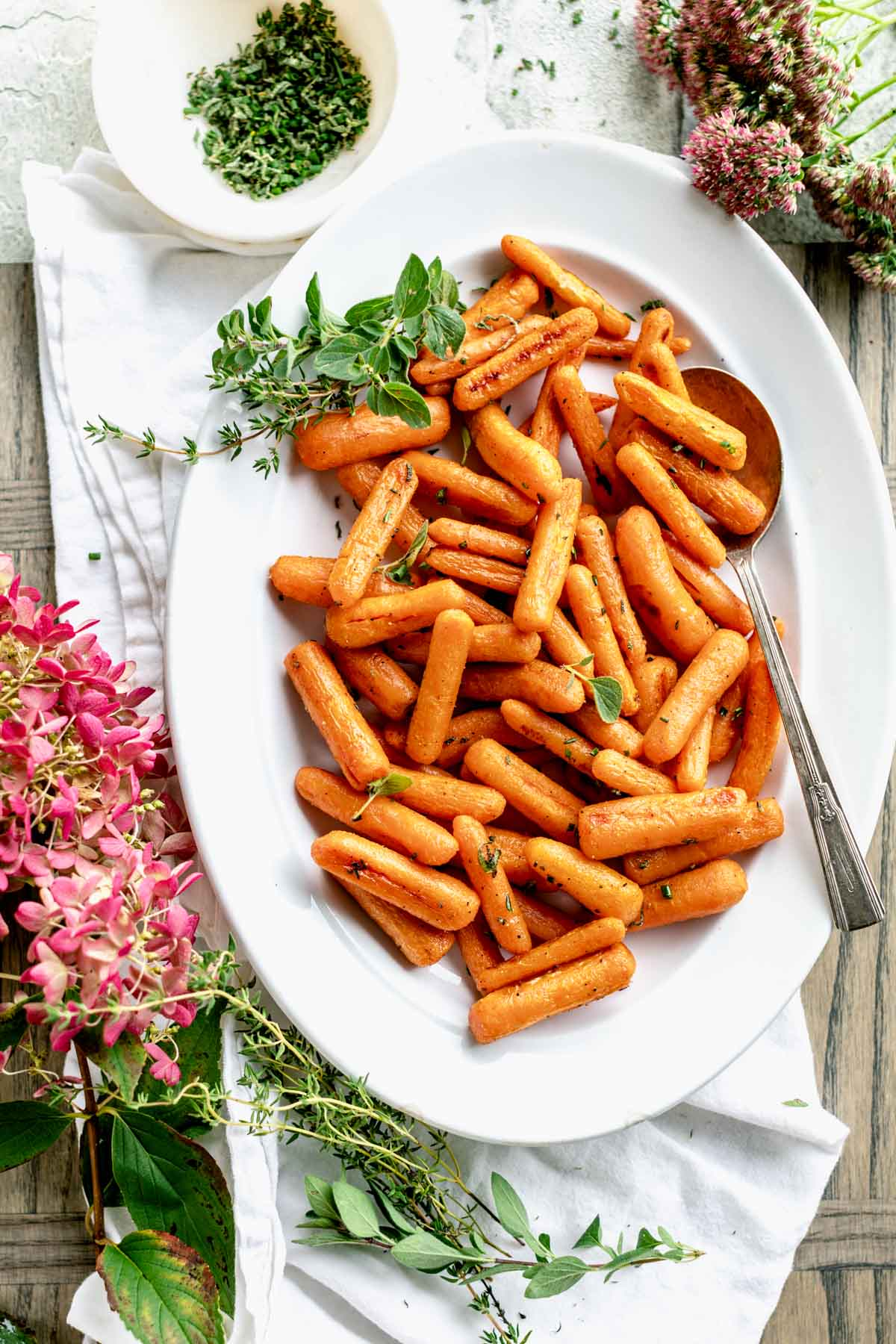 an oval platter with roasted baby carrots on it