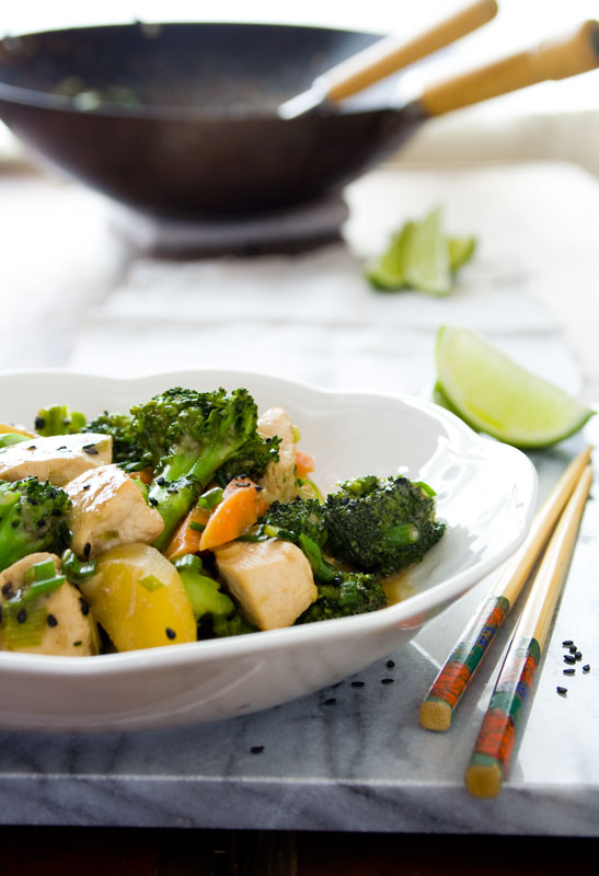 Broccoli Chicken stirfry in a white bowl with chopsticks