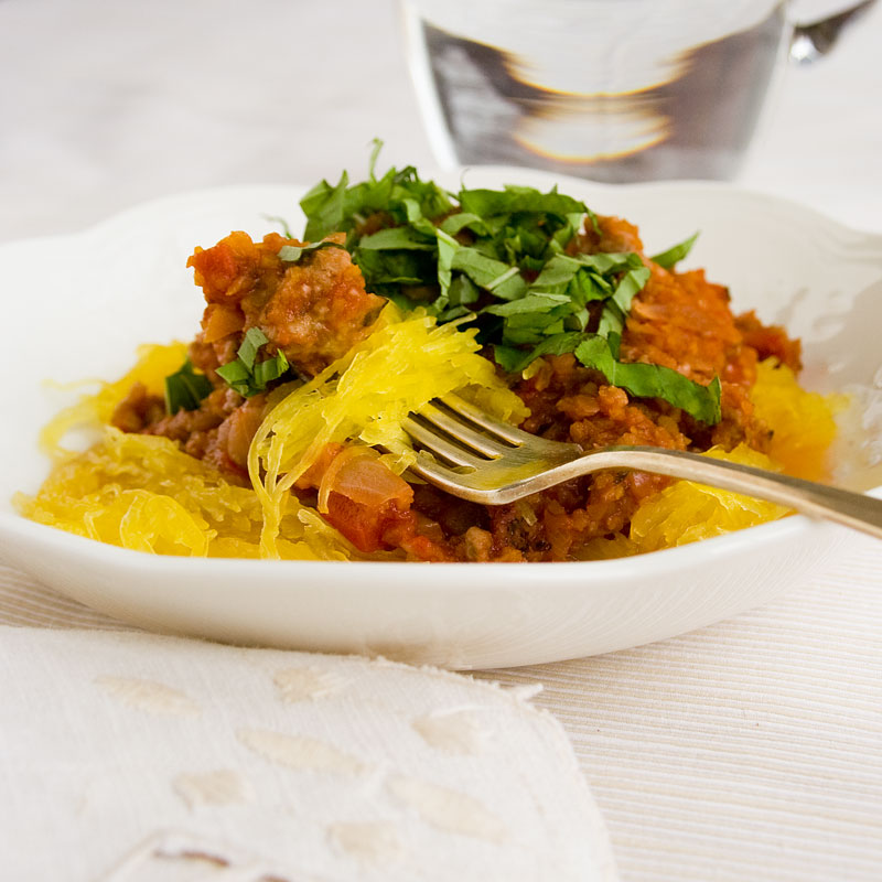 spaghetti squash with meat sauce and basil in a bowl