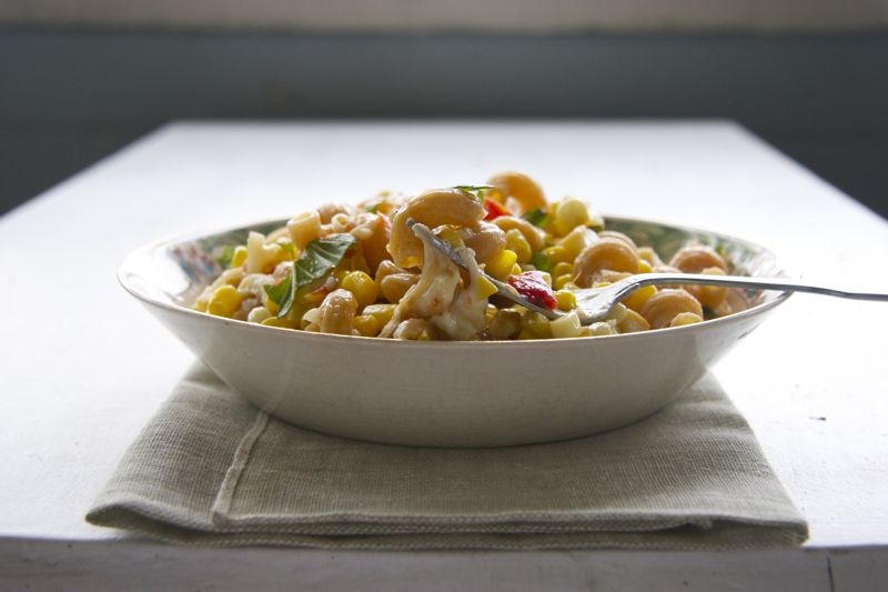 A bowl of food on a plate, with Corn and Pasta